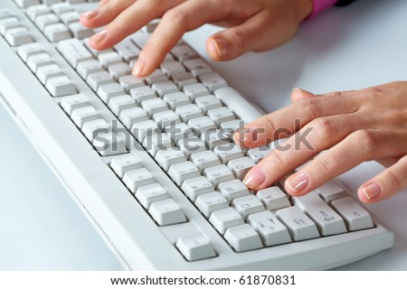 Close-up of a keyboard and female hands typing on it - stock photo