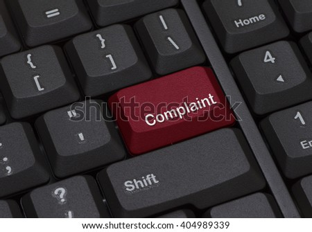 Close up of a keyboard with red enter button written COMPLAINT - stock photo