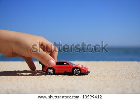 Close-up of a kid hand playing with a racing car - stock photo