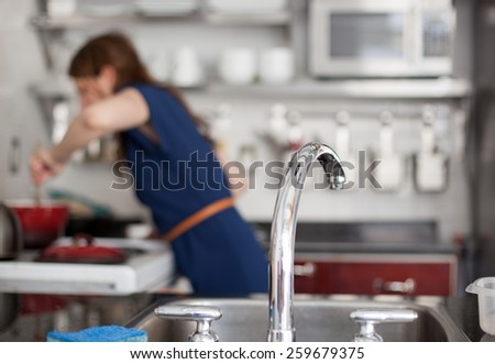 Close up of a kitchen faucet with woman cooking in the background - stock photo