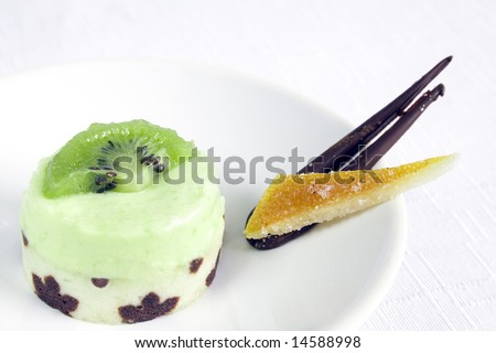 Close up of a kiwi petit four on a white dish and background. Main focus on the middle part of the PF. It's accompanied with a slice of glazed orange skin and a piece of chocolate. - stock photo