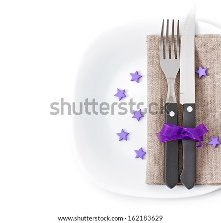 Close up of a knife and fork on a white plate with napkin on the white background - stock photo