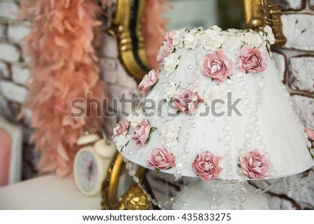 Close-up of a lampshade with pink roses and beads on the ladies' table with a mirror in a gold frame curly