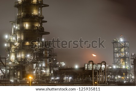 Close-up of a large oil-refinery plant at night - stock photo