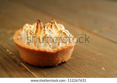 Close up of a lemon pie on a wooden table - stock photo