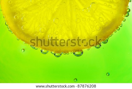 Close-up of a lemon slice with bubbles - stock photo