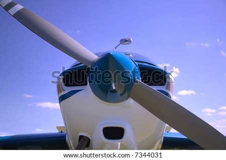Close up of a light aircrafts nose cone against a blue cloudy sky. - stock photo