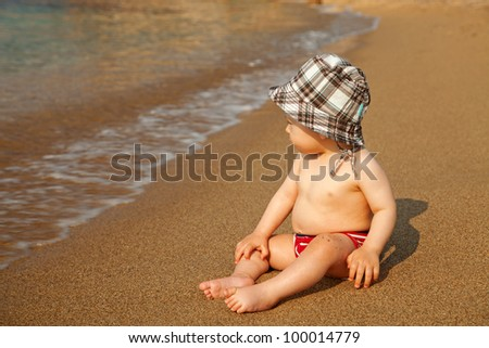 Close up of a little baby sitting on the beach and enjoying sea waves - stock photo