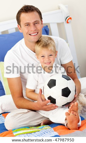 Close-up of a little boy and his father playing with a soccer ball sitting on bed - stock photo