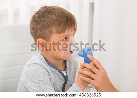 Close-up Of A Little Boy Inhaling Through Oxygen Mask In Clinic