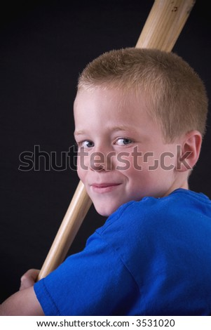 Close-up of a little boy with a baseball bat. - stock photo