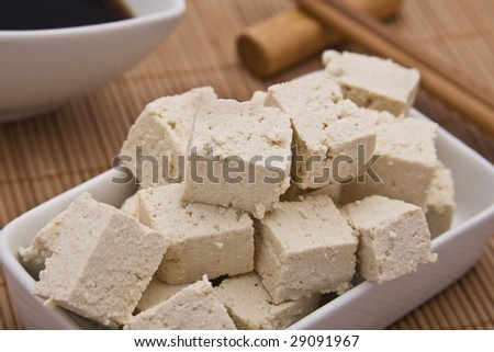 Close up of a little dish with tofu cubes. Shallow dof, focus on cubes at the front. - stock photo