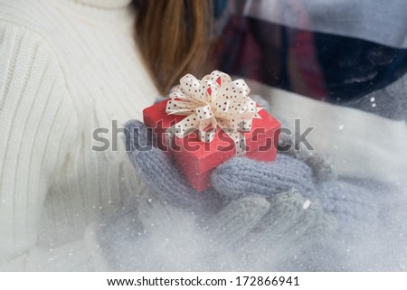 Close-up of a little giftbox in hands in mittens