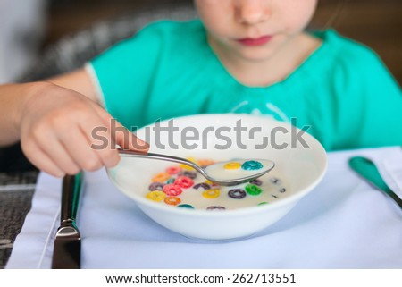 Close up of a little girl eating cereal with milk for breakfast in restaurant - stock photo