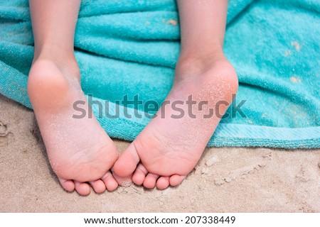 Close up of a little girl feet on a beach towel - stock photo