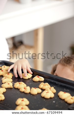 Close up of a little girl taking a cookie in the kitchen while her parents are cooking - stock photo