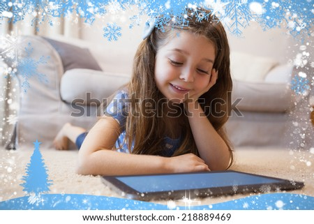 Close up of a little girl using digital tablet in living room against snow - stock photo