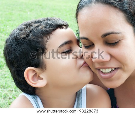 Close up of a little hispanic boy kissing their mother - stock photo
