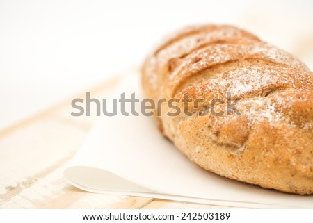 Close up of a loaf of wheat bread on painted wood background for a healthy diet  - stock photo