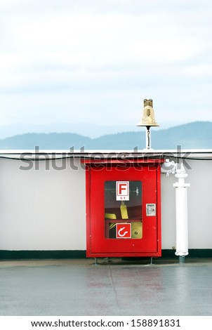 Close-up of a locked, alarmed fore hose box on a bridge. Mountains in the horizon. - stock photo