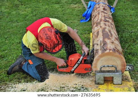 Close up of a logger using a chainsaw in a logging competition. Sawdust flying. - stock photo