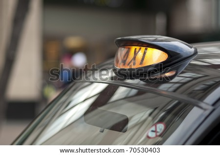 Close up of a London black cab with yellow light on. - stock photo