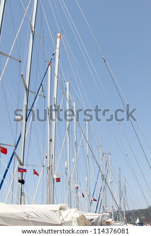 Close-up of a lot of masts against the sky, folded sails