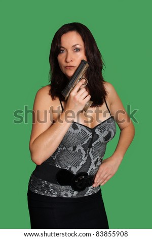 Close-up of a lovely, busty brunette holding a gun, isolated on a green background. - stock photo