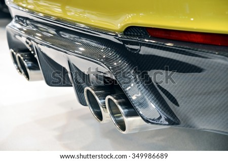 Close up of a luxury sportive car with four exhaust pipe and bumper realized in real carbon fiber. - stock photo