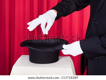 Close-up Of A Magician Performing Magic With Hat - stock photo