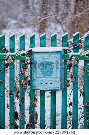 Close up of a mailbox on the street with aqua fence - stock photo