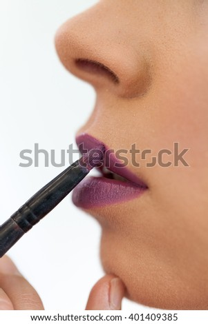 Close up of a make-up artist contouring lips to model. Selective focus - stock photo