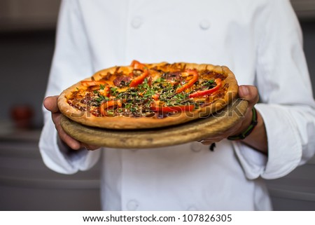 Close-up of a male chef preparing a pizza in a kitchen - stock photo