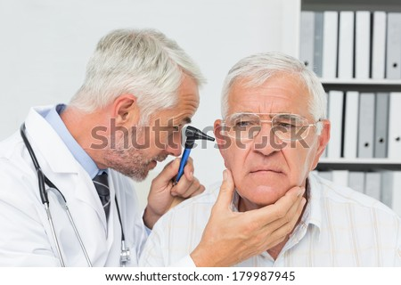 Close-up of a male doctor examining senior patient's ear at the medical office - stock photo