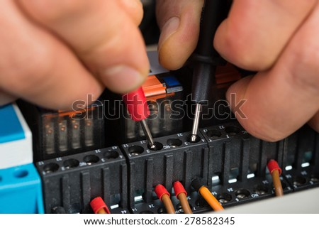 Close-up Of A Male Electrician Checking Fuse With Multimeter - stock photo