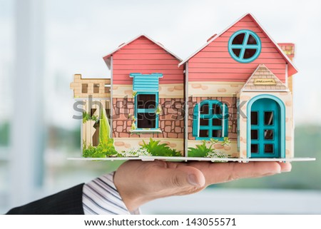 Close-up of a male hand holding a house miniature - stock photo