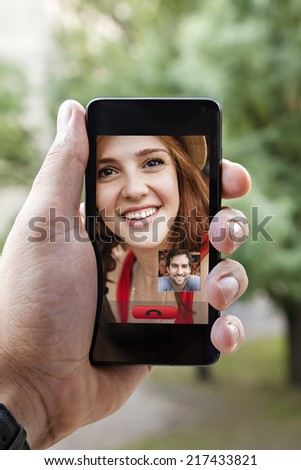 Close Up Of A Male Hand Holding A Smart Phone During A Video Call With His Girlfriend - stock photo