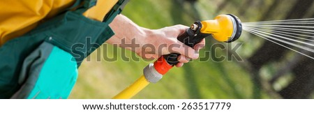 Close-up of a male hand with a hose watering grass - stock photo