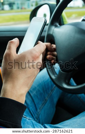 Close up of a male hand with smartphone in the car - stock photo