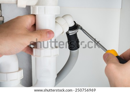 Close-up Of A Male Plumber Repairing Sink In Bathroom - stock photo