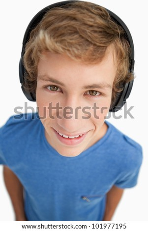 Close-up of a male student wearing headphones against white background