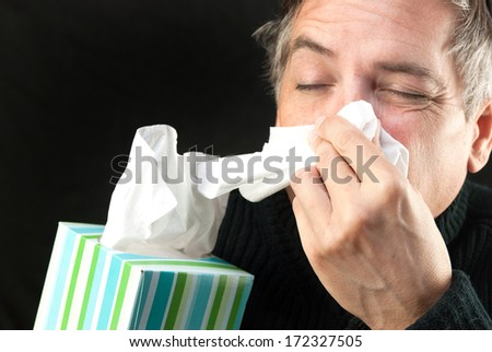 Close-up of a man blowing his nose while holding a tissue box. - stock photo