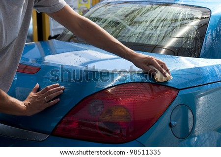 Close-up of a man cleaning his car - stock photo