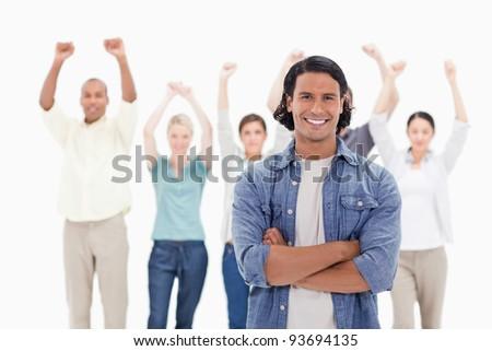 Close-up of a man crossing his arms with people raising their arms in background - stock photo