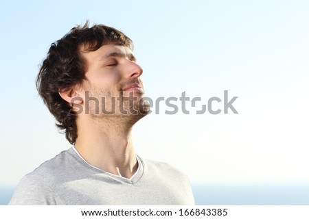 Close up of a man doing breath exercises outdoor with the sky in the background                - stock photo