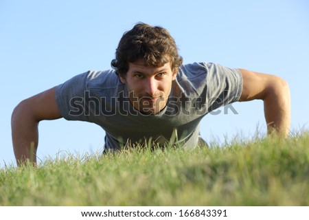 Close up of a man doing pushups on the grass with the horizon in the background - stock photo