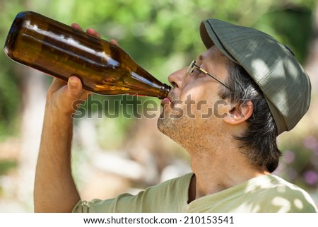 Close up of a man drinking beer from bottle outdoors. - stock photo