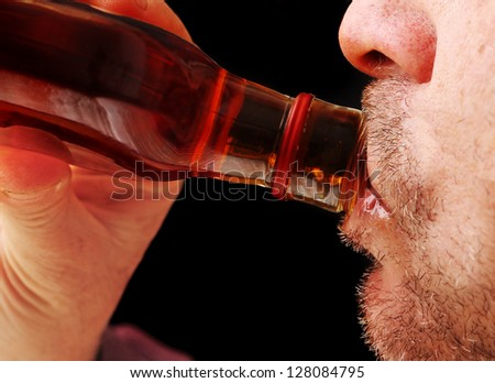 Close Up of a Man Drinking Hard Liquor from the Bottle - stock photo