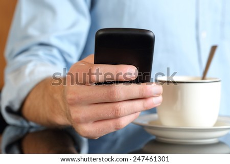 Close up of a man hand using a smart phone at breakfast with a coffee cup in the background - stock photo