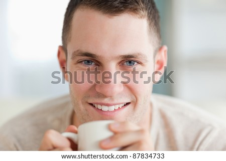 Close up of a man having a tea in his living room - stock photo
